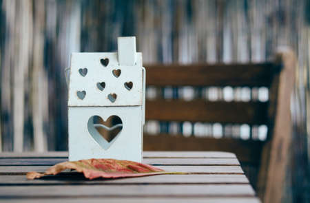 A soft focus shot of a house shaped lantern with heart holes on a wooden table 免版税图像