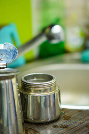 A soft focus shot of a newly washed silver moka pot beside a kitchen sink