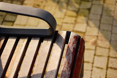 A high angle closeup shot of a wooden bench and the cobblestone ground below