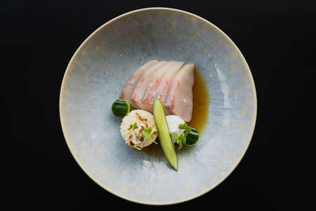 A top view of a fresh salad with sliced kingfish, cucumber and rice