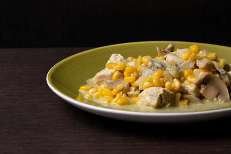A closeup of a delicious dish with mushrooms, chicken, and corn on a plate on the table