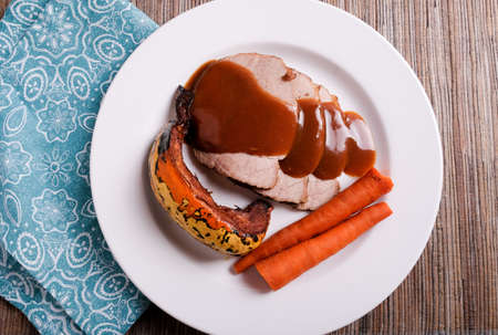 A closeup shot of roasted pork, gravy, acorn squash, and carrots in a white plate