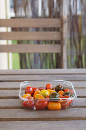 A vertical shot of different types of tomatoes in a plastic box Banco de Imagens