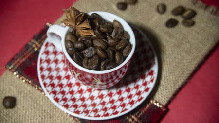 A selective focus shot of coffee beans and star anise in a Christmas coffee cup