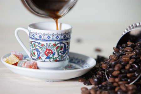 A closeup shot of the person pouring coffee into the cup