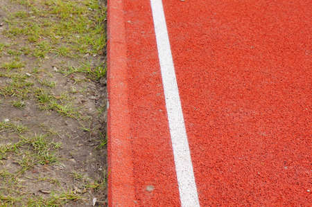 A closeup of the edge of an all-weather running track