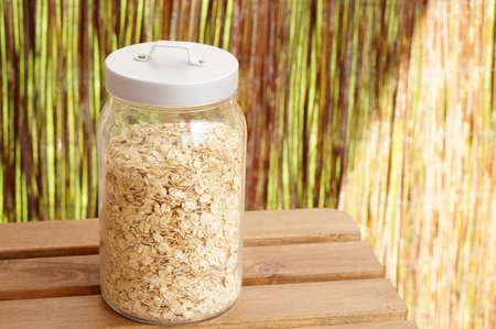 A glass jar filled with oat flakes on a wooden surface Banco de Imagens