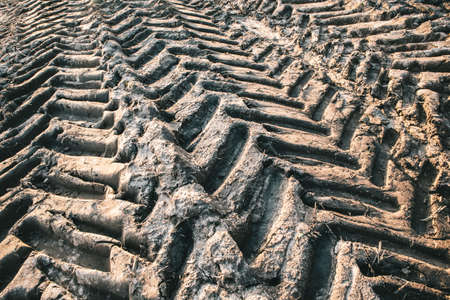 A closeup shot of tractor tire tracks on a muddy ground