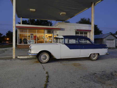 MONTGOMERY CITY, UNITED STATES - Sep 04, 2014: Photo of vintage 1955 Pontiac parked at an old gas station at dusk in small Missouri town.