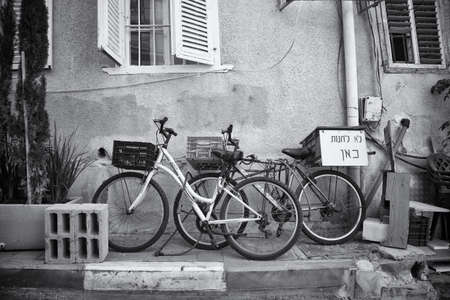 A greyscale shot of two bicycles parked near the building in Tel, Aviv, Israel