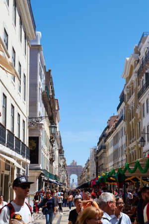 LISBON, PORTUGAL - Jun 11, 2019: Wide angle shot taken from the busy streets of lisbon portugal with the Arco da Rua Augusta far in the back ground Redakční