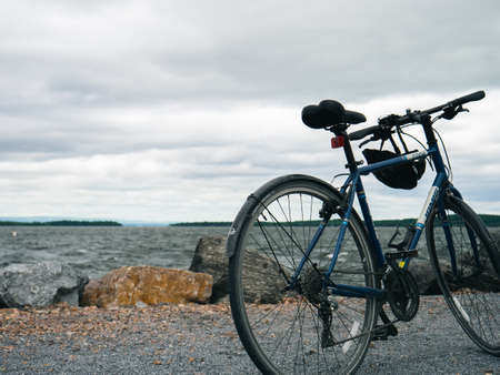 A blue mountain bike parked on a sea shore under a cloudy sky