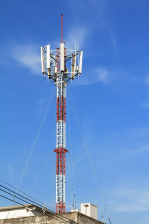 Red and white roof top cellular tower under clear sky photo