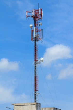 Red and white roof top cellular tower under blue sky photo