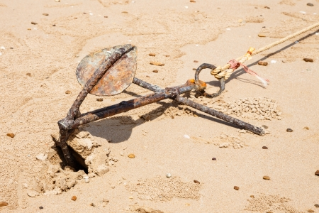 Small rusty traditional anchor on a beach photo