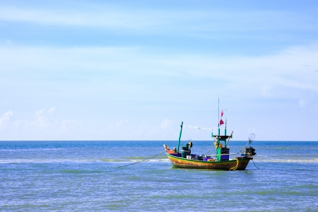 Traditional fishing boat anchoring near a beach photo