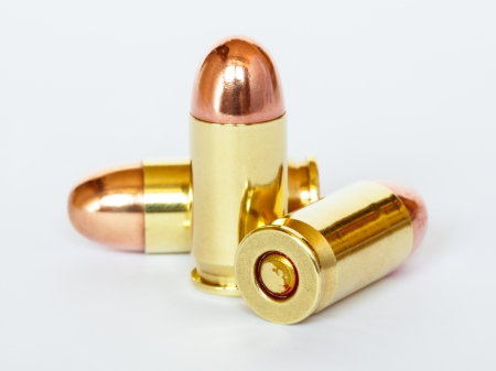 Three 9 mm or .357 bullet on white background photo