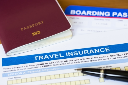travel agent: Travel insurance application form with pen and passport