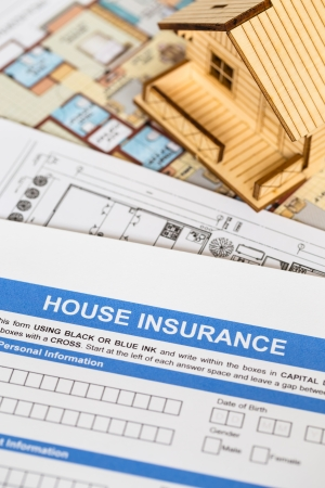 House insurance application with model house and construction plan photo