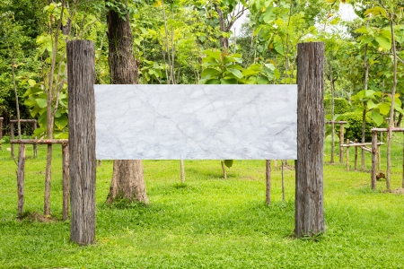 Blank weathered wooden sign with marble board in a park photo