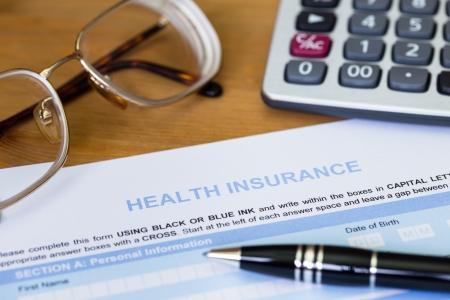 salute: Modulo di domanda di assicurazione sanitaria con la penna, calcolatrice e bicchieri Archivio Fotografico