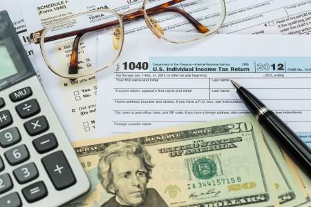 Belasting formulier met pen, rekenmachine, dollar biljet, en glazen belastingen begrip