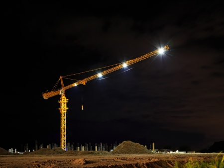Yellow tower crane at construction site by night time