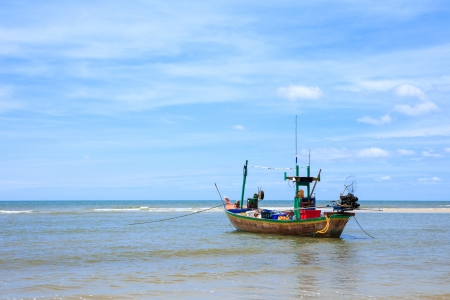 Traditional fishing boat floating on water, blue sea and sky photo