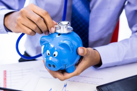 Businessman use stethoscope with piggy bank for financial health check concept Standard-Bild