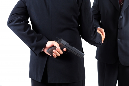 intention: Businessman hiding gun while handshaking concpet for dishonesty Stock Photo