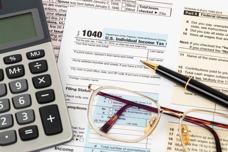 the income: Formulario de impuestos con la pluma, calculadora y gafas concepto de impuestos Foto de archivo