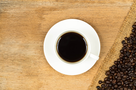 Coffee cup and roasted beans over hessian on wooden table photo