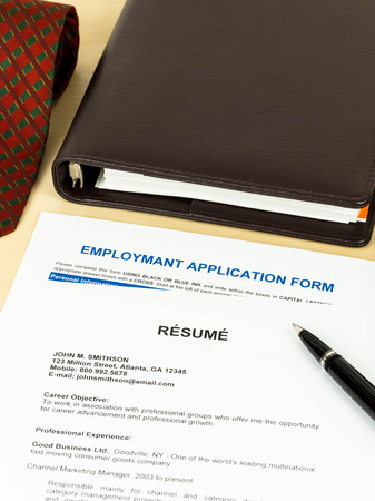 Resume with employment application form, pen, neck tie, and notebook photo