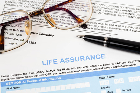 Life assurance application form with pen and glasses concept for life planning photo