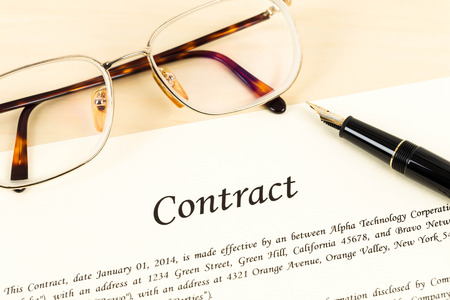 Business contract document on cream color paper with pen and glasses photo
