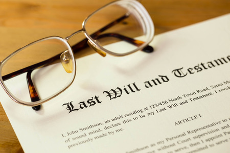financial official: Last will and testament on cream color paper with glasses