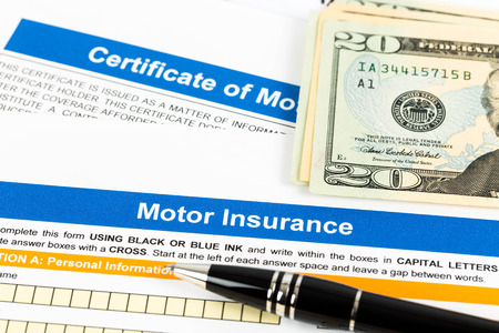 Motor or car insurance application with pen, and dollar banknote photo