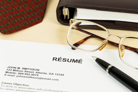 Resume, pen, neck tie, glasses, and notebook photo