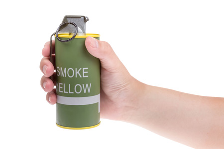 Yellow smoke grenade  in hand isolated on white photo