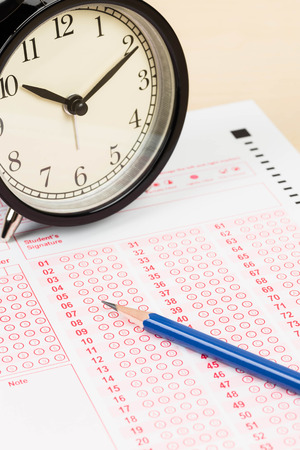Answer sheet with pencil and alarm clock Stock Photo