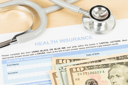 Health insurance application form with banknote and stethoscope concept for life planning photo