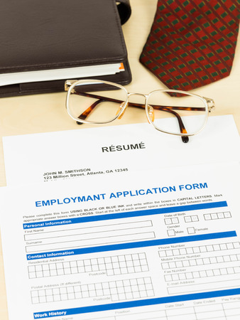 Application form, resume, neck tie, glasses, and planner photo