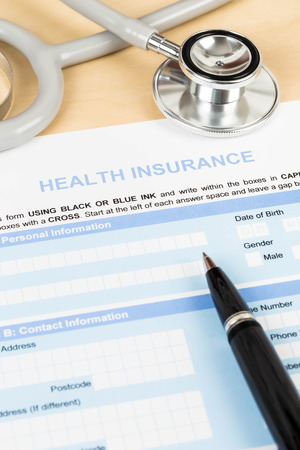Health insurance application form with pen and stethoscope concept for life planning