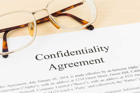 Confidentiality agreement document with glasses close-up