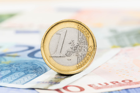 Euro money banknote and coin close-up (focus on coin) photo