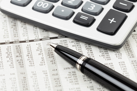 stock price: Pen, and calculator rest on stock price detail financial newspaper