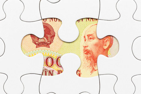 dong: Vietnamese dong banknote hidden under puzzle financial concept