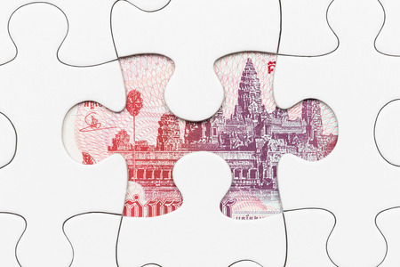 riel: Cambodia riel banknote hidden under puzzle financial concept