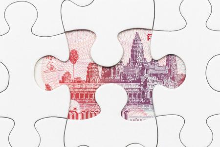 Cambodia riel banknote hidden under puzzle financial concept