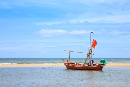 old boat: Traditional fishing boat on beach and blue sky